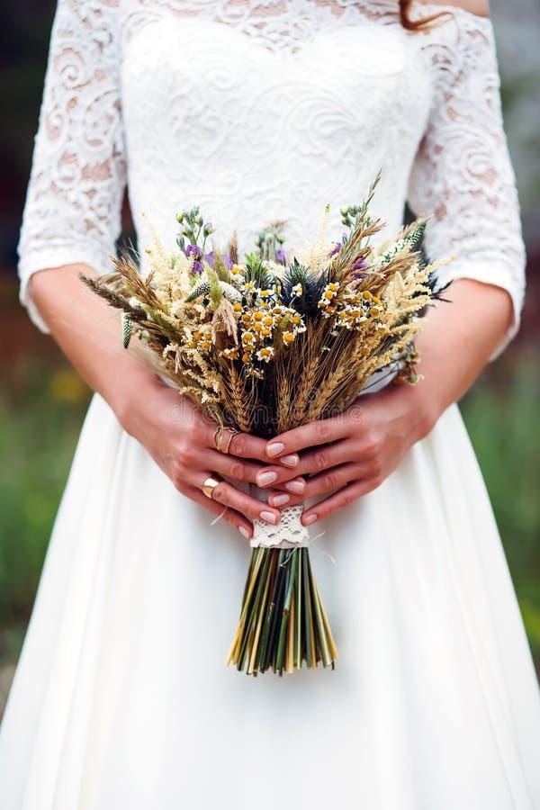 花束干花在新娘的手上 免版税库存照片