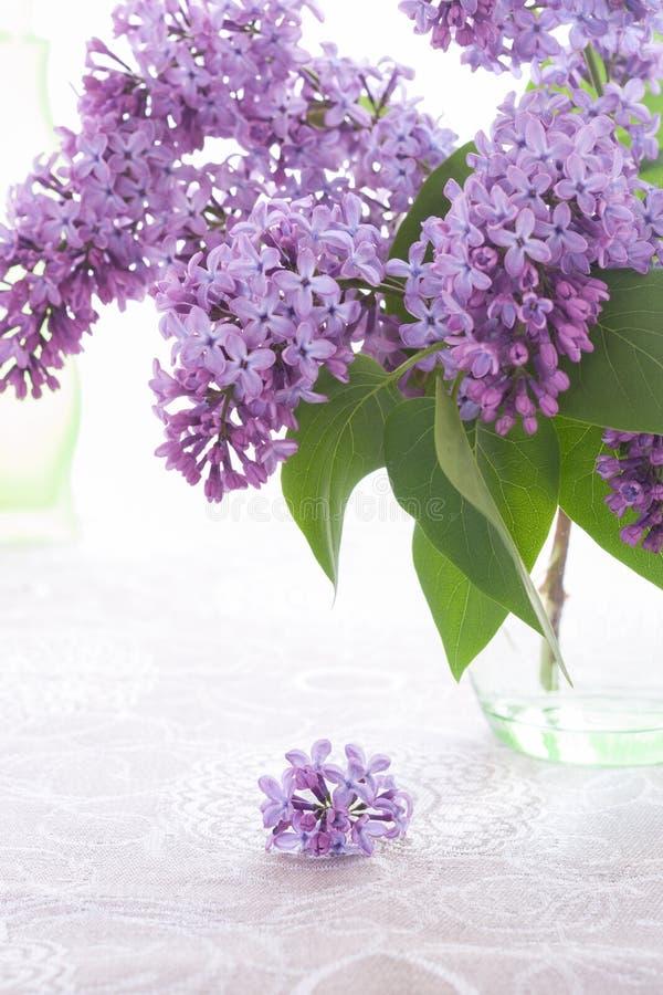 花束或紫色丁香在绿色玻璃花瓶站立,并且小开花在胡麻桌布说谎 免版税图库摄影