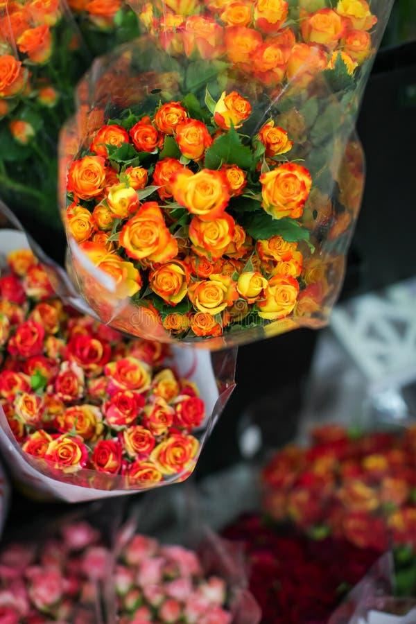花束玫瑰在卖花人` s的待售在街道与透明包装纸的花市场上购物 库存图片