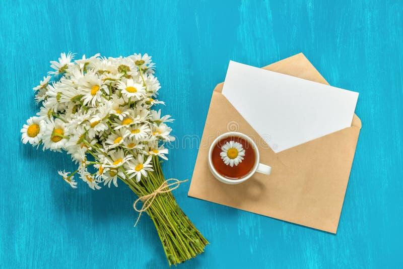 花束白色春黄菊开花杯子药草浸剂和信件cra 免版税库存照片