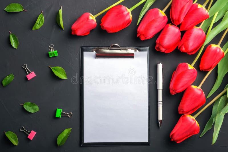 花束红色郁金香和绿色叶子顶视图大模型在黑背景与剪贴板和笔 免版税库存照片