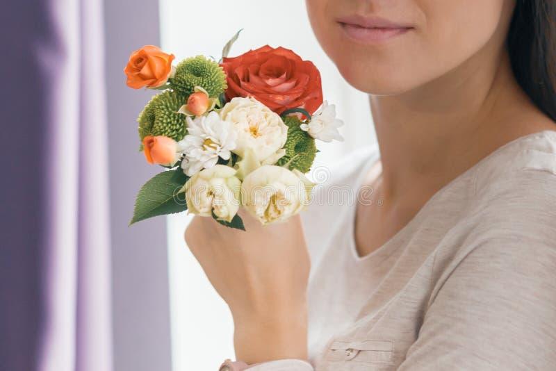 花束花在手中年轻微笑的妇女特写镜头  免版税库存照片