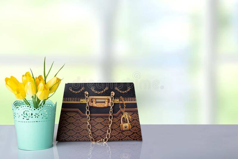 花束黄色郁金香和一个棕色礼物纸袋在桌上为 免版税库存图片