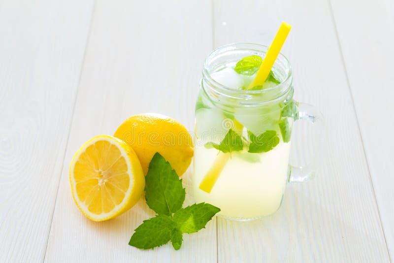 花梢凉快的杯与冰和薄菏,金属螺盖玻璃瓶样式杯子的柠檬水有黄色秸杆的,新鲜薄荷绿色叶子和柠檬,一 免版税图库摄影