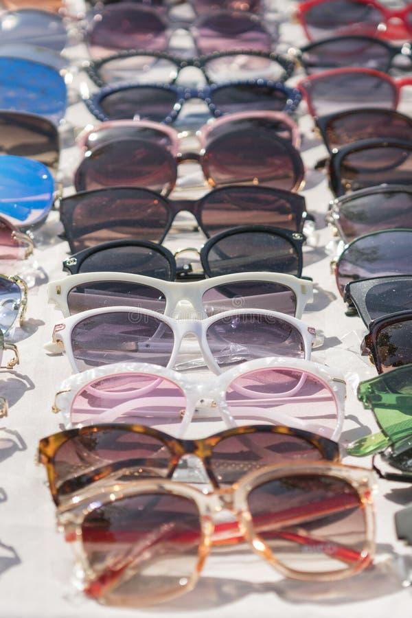 花梢太阳镜在商店 时尚太阳镜在商店 太阳镜的异常和原始的收藏 r 免版税库存照片