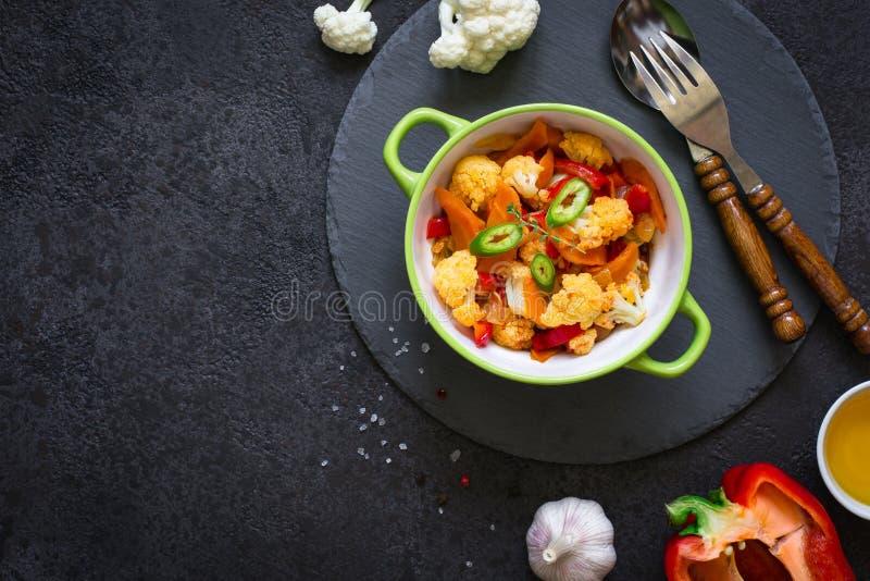 花椰菜、红萝卜和蕃茄菜炖煮的食物在黑背景 库存照片