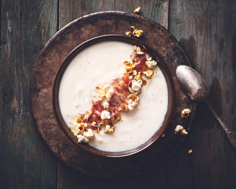 花椰菜乳脂状的汤用咖喱玉米花和斑点火腿 免版税库存照片