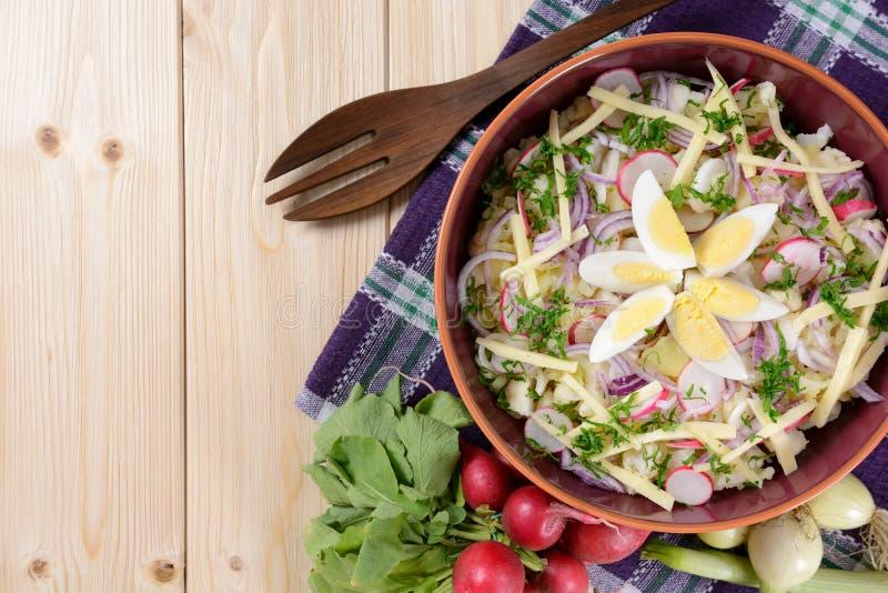 花椰菜沙拉用土豆、不幸、鸡蛋、红洋葱和萝卜 免版税图库摄影