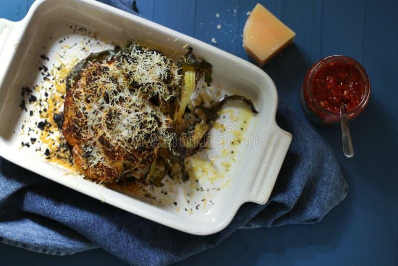 花椰菜烘烤了整个与辣椒油并且磨碎了巴马干酪 免版税库存照片
