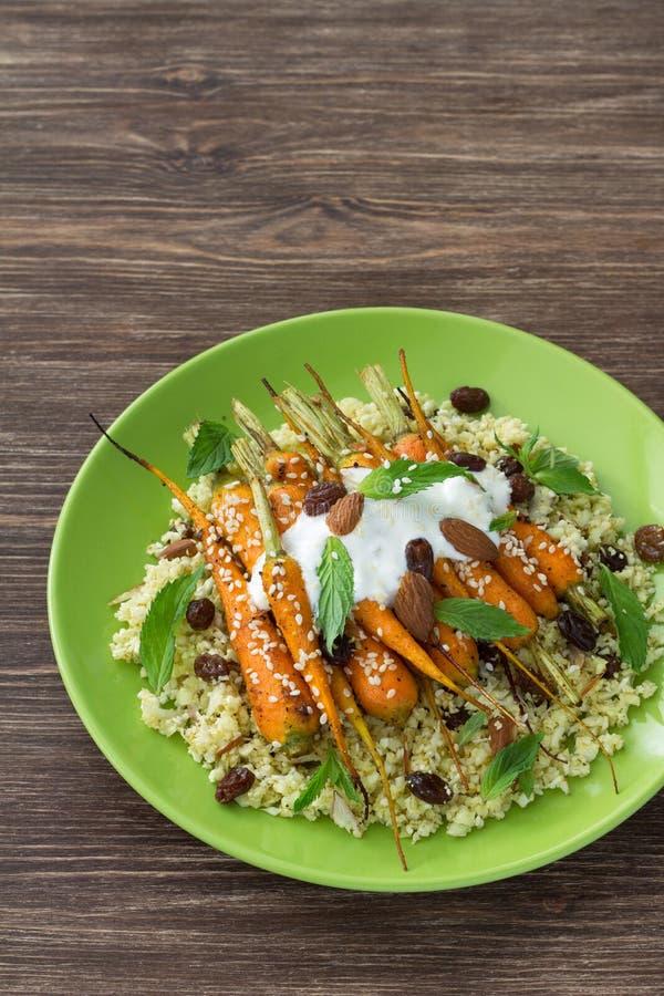 花椰菜蒸丸子用在一块陶瓷板材的被烘烤的嫩胡萝卜 图库摄影