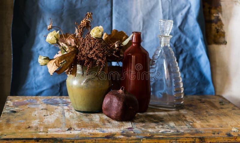 花瓶、瓶、石榴和凋枯的花的构成 免版税库存照片