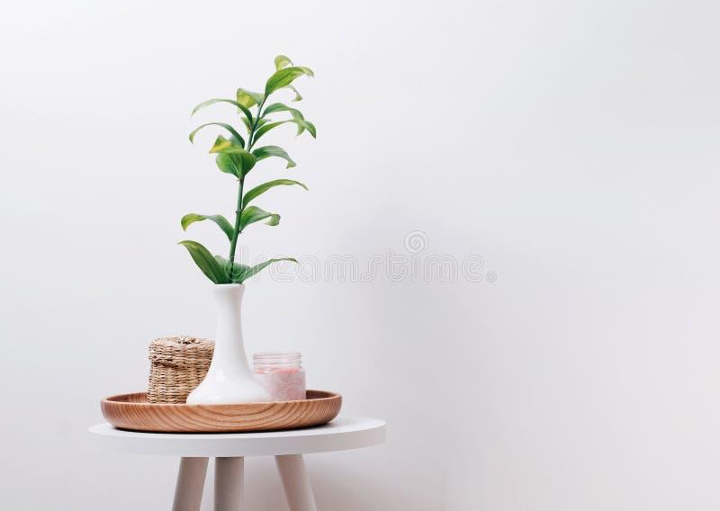 花瓶、蜡烛和秸杆箱子的绿色植物在小桌上 免版税图库摄影