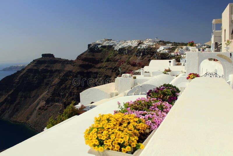 花瓶在使圣托里尼海岛背景惊奇的五颜六色的花 库存照片