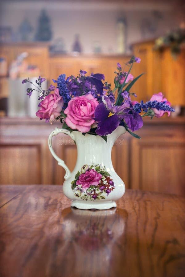 花瓶在厨房用桌上的花 免版税库存图片