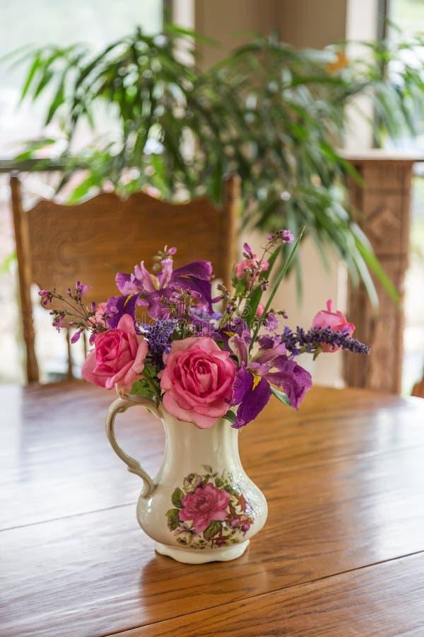 花瓶在厨房用桌上的花 免版税库存照片