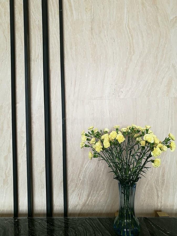 花瓶在大理石酒吧的右边的黄色康乃馨花在旅馆大厅的有迷离背景,旅馆装饰 免版税库存照片