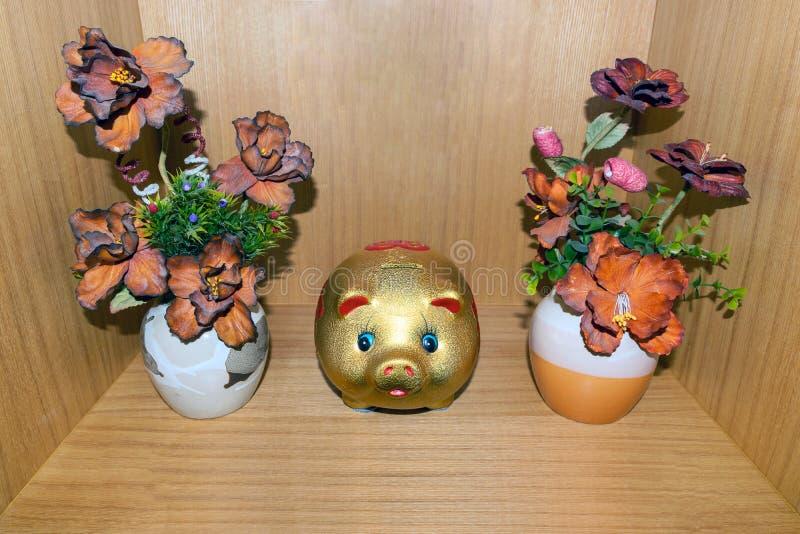 花瓶塑料花和存钱罐 免版税库存照片