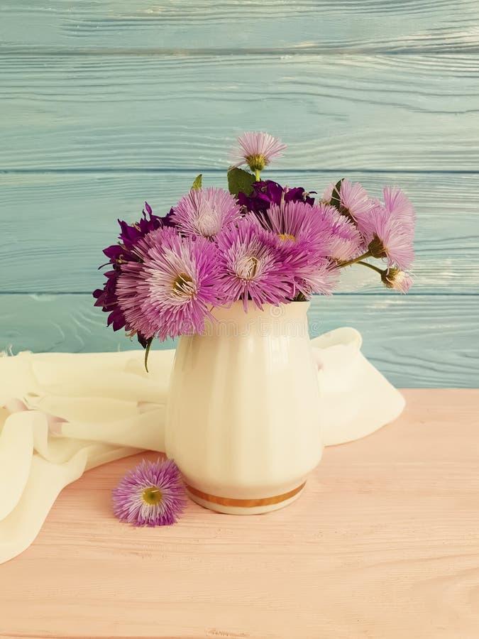 花瓶开花响铃,紫色在木背景的高雅秀丽装饰春天菊花安排 免版税库存图片