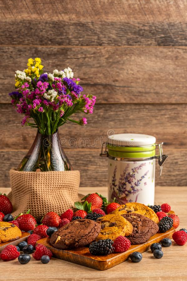 花瓶用狂放的莓果和巧克力饼干在船上 免版税库存图片
