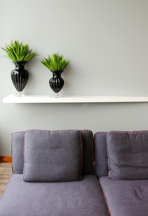 花瓶的绿色植物与方便的沙发 免版税库存图片