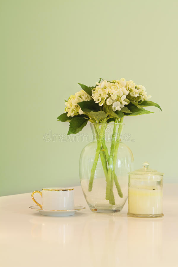 花瓶花和茶杯在软的绿色淡色颜色 免版税库存图片
