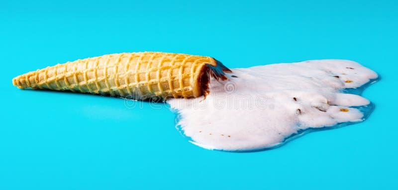 花生在蓝色背景在的冰淇淋锥体熔化的 库存图片
