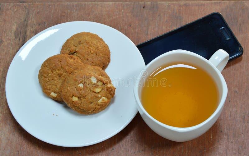 花生曲奇饼和茶与黑手机的 免版税库存照片