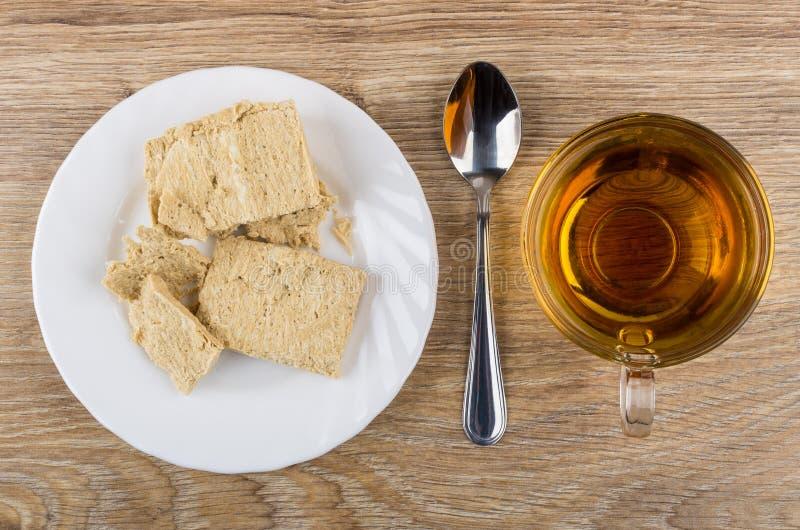 花生halva片断在板材、茶和茶匙的 免版税图库摄影