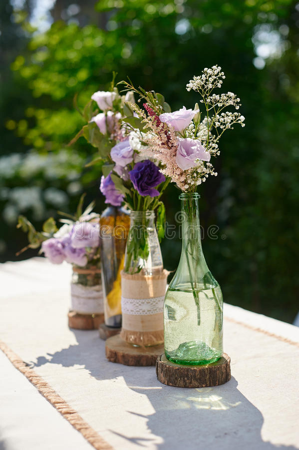 花的婚礼装饰在一个瓶的在桌上 免版税库存图片