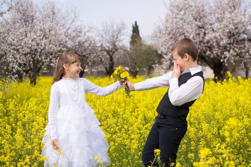 给花的害羞的男孩 免版税图库摄影