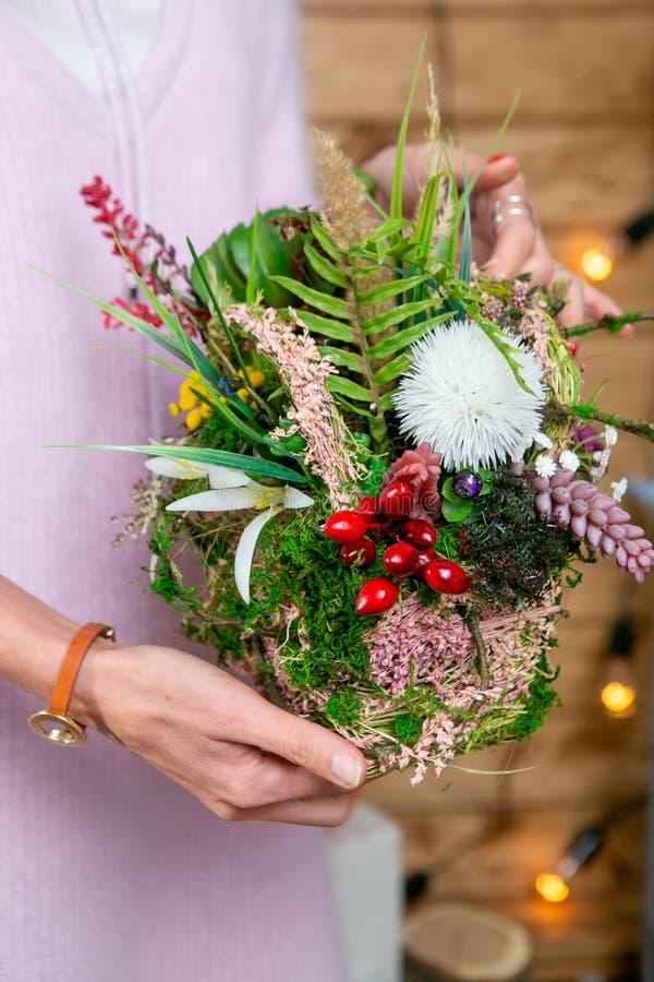 花的布置在卖花人的手上在完成阶段  免版税库存照片