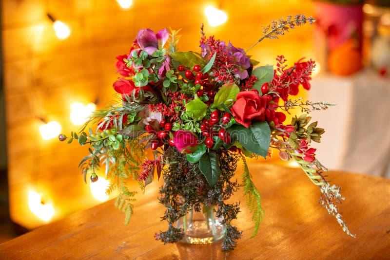 花的布置用红色莓果、英国兰开斯特家族族徽和绿色在桌上 免版税库存照片