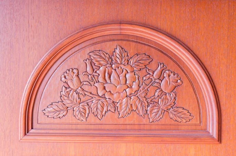 花的样式在棕色木背景雕刻了 免版税库存照片