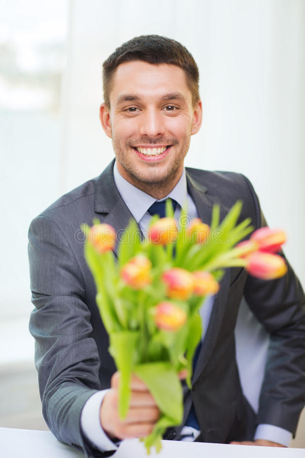 给花的花束微笑的英俊的人 免版税库存照片