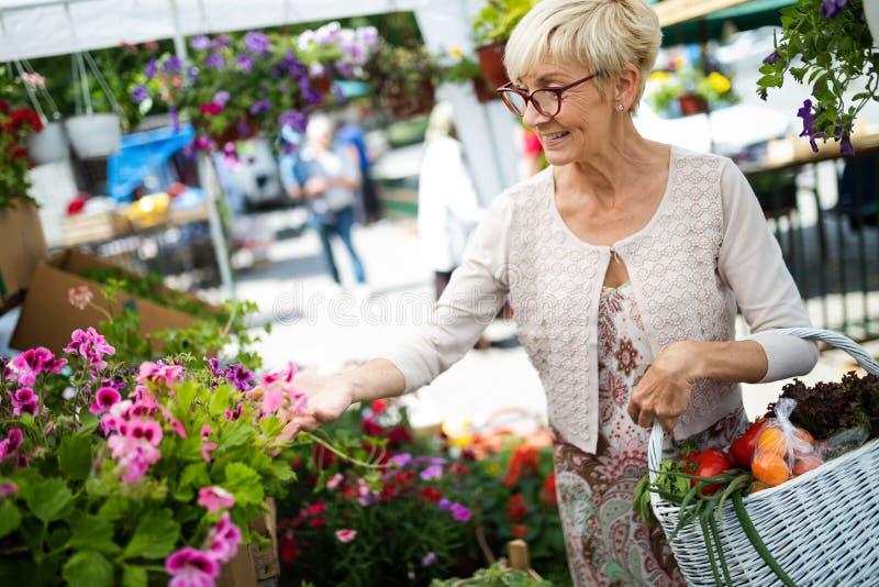 花的资深夫人购物在园艺中心微笑 库存图片