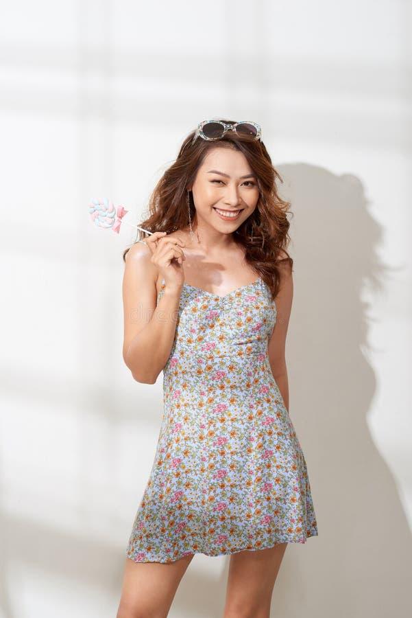 花礼服的可爱的亚裔妇女有棒棒糖的在手中 免版税库存图片