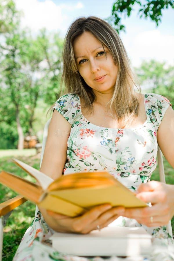 花礼服看书的一名妇女和坐室外 免版税库存照片