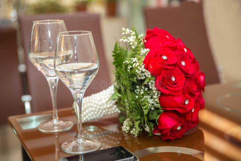 花红色婚礼花束  英国兰开斯特家族族徽和两块站立在地道的香槟玻璃婚礼花束  背景wi 图库摄影