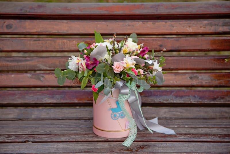花美丽的嫩花束在桃红色箱子的在木backgr 免版税库存照片