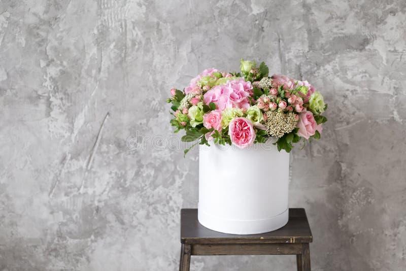 花美丽的嫩花束在白色箱子的在与空间的灰色ackground文本的 免版税库存照片