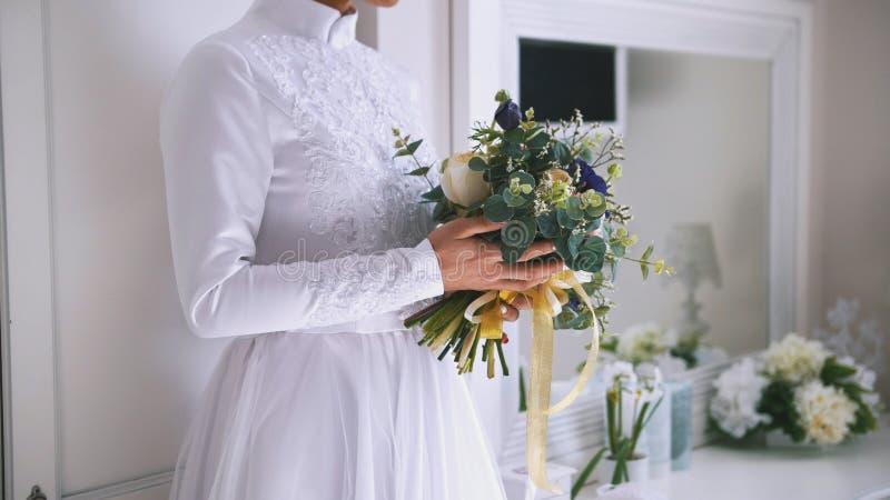 花美丽的花束在年轻新娘的手上在白色婚礼礼服穿戴了 免版税库存照片