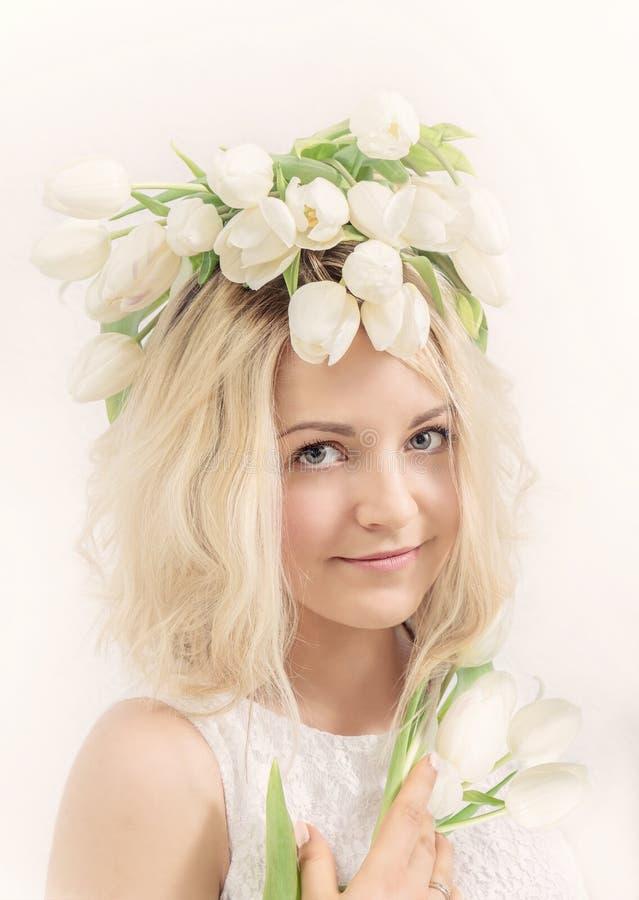 花花圈的少妇  背景概念花春天空白黄色年轻人 免版税库存照片