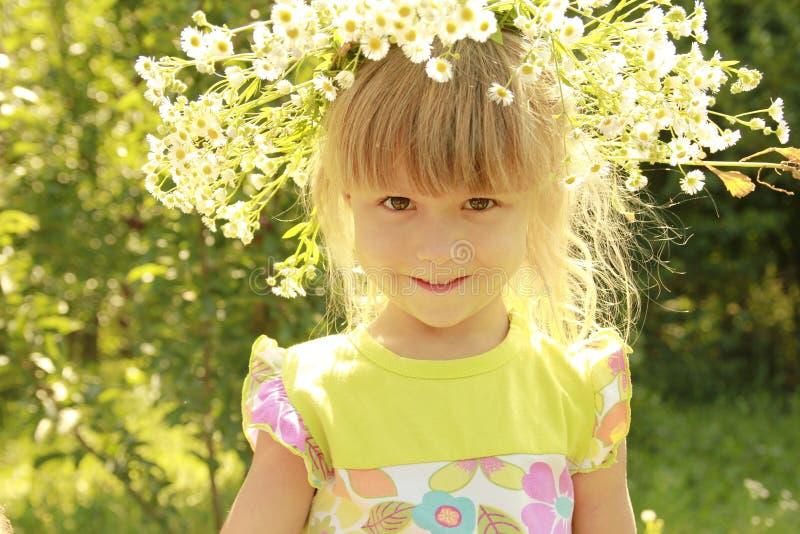花花圈的美丽的小女孩在自然的 免版税库存图片