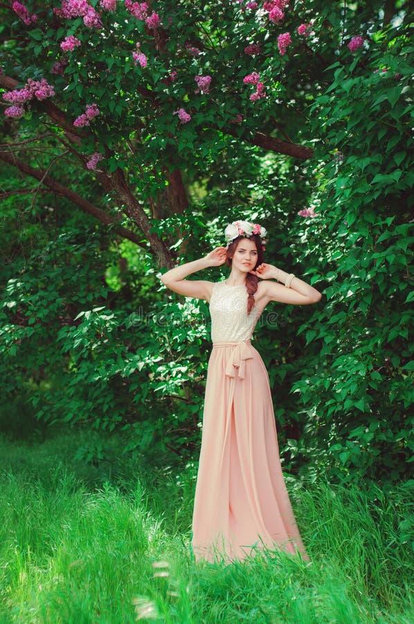 花花圈的年轻美丽的女孩在庭院里 免版税库存图片