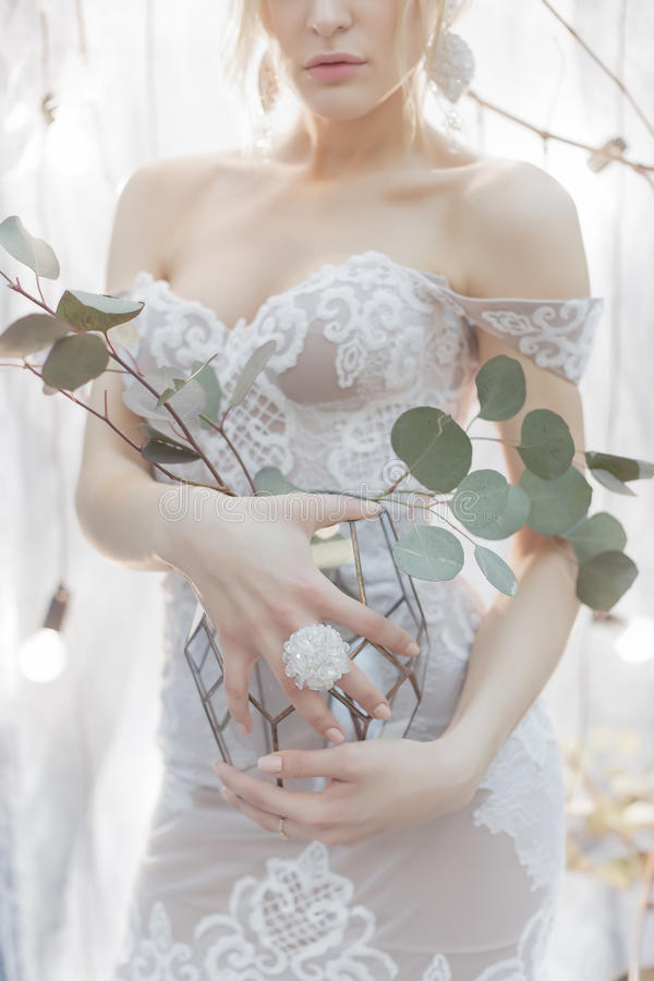 花花束在拿着一套典雅的白色婚礼礼服的花瓶的一个女孩新娘与在他的手指的一个大圆环 免版税图库摄影