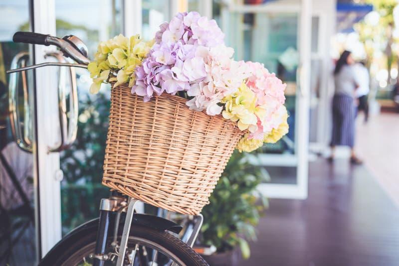 花花束在桶的在葡萄酒自行车前面  庭院 库存图片