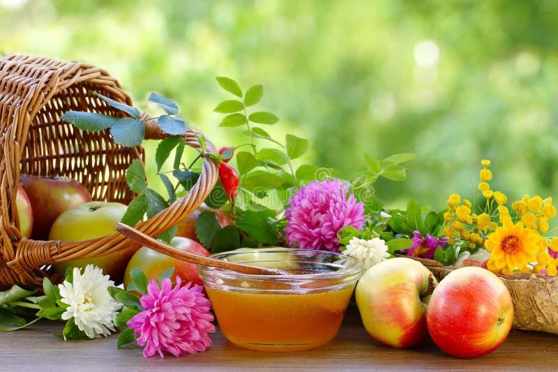 花蜂蜜、苹果和庭院花 仍然生活夏天 被弄脏的背景 库存照片