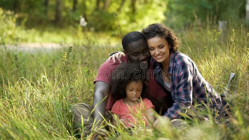 花费他们的与一点女儿的家庭夫妇时间,放松在公园 库存图片
