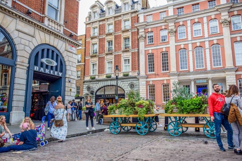 花费他们的时间的游人在科文特花园市场上在伦敦,英国 库存照片