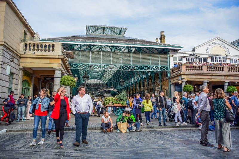 花费他们的时间的游人在科文特花园市场上在伦敦,英国 免版税库存照片